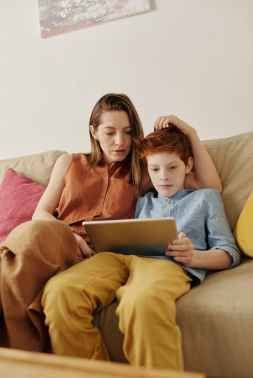 photo of woman and boy watching through tablet computer